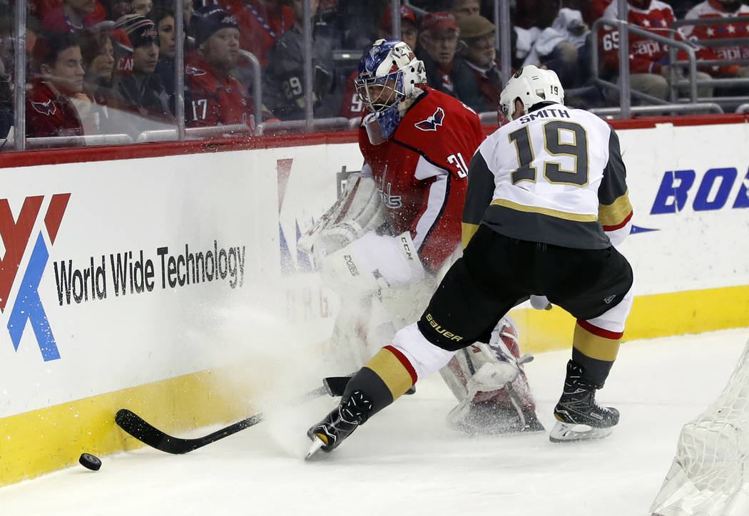 Washington Capitals goaltender Philipp Grubauer (31), from Germany, knocks the puck away from Vegas Golden Knights right wing Reilly Smith (19) in the first period of an NHL hockey game, Sunday, F ...