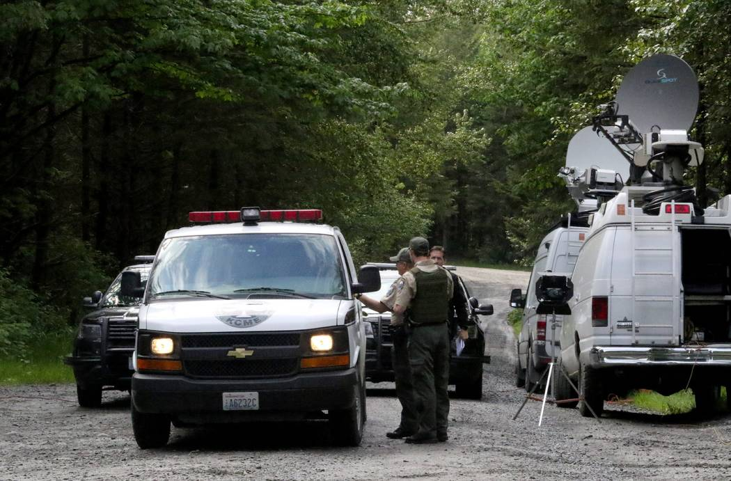 Washington State Fish and Wildlife Police confer with an individual from the King County Medical Examiner's office on a remote gravel road above Snoqualmie, Wash., following a fatal cougar attack, ...