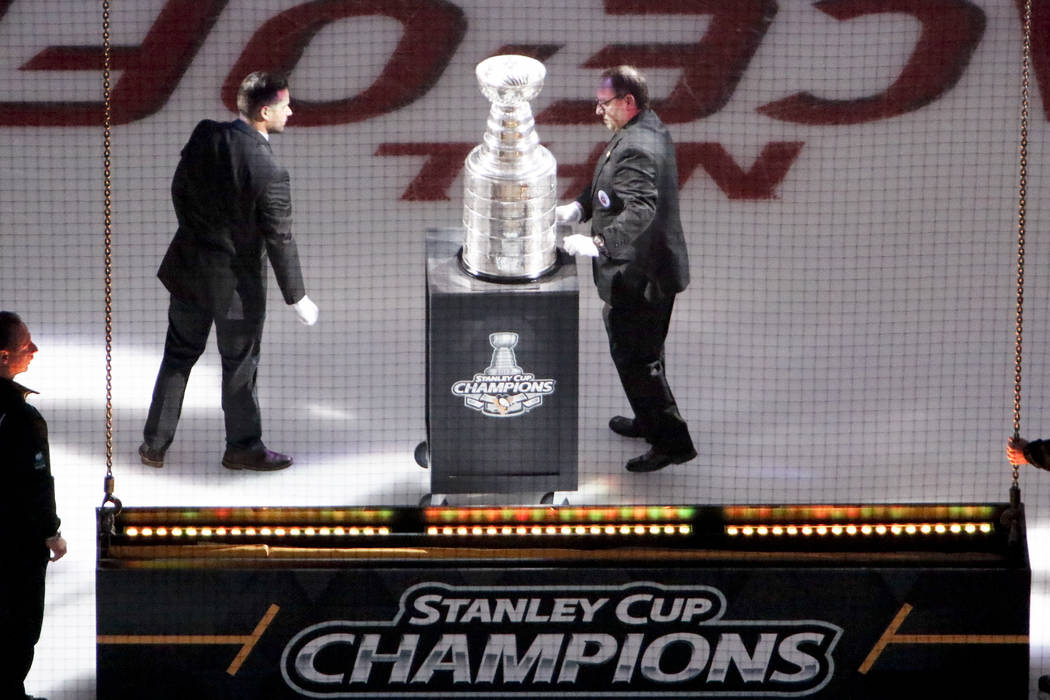 Handlers move the Stanley Cup into position before the banner for their fifth Stanley Cup Championship is raised before the NHL hockey game against the St. Louis Blues, Wednesday, Oct. 4, 2017, at ...