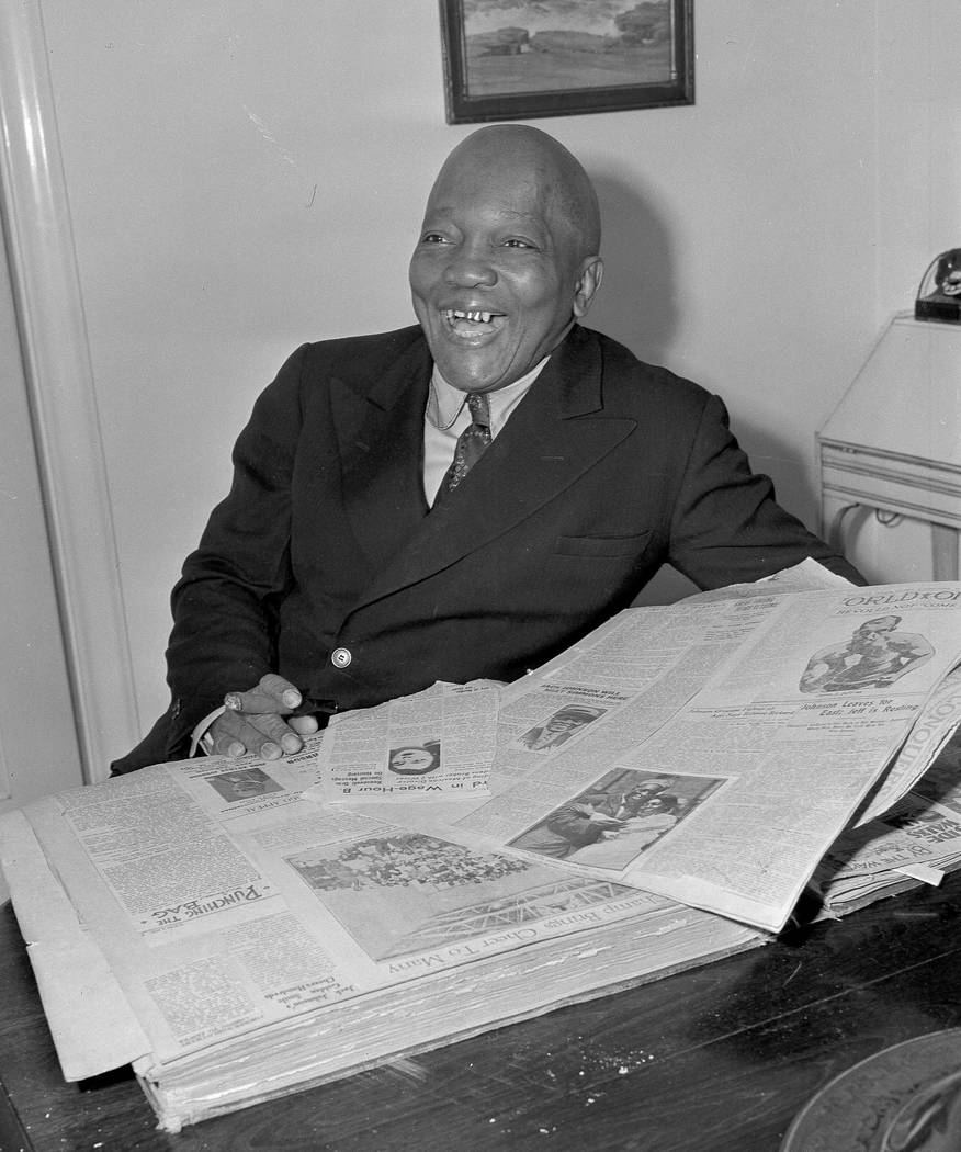 FILE In this Feb. 10, 1943, file photo, former boxer Jack Johnson looks through a scrapbook of newspaper clippings in Los Angeles. President Donald Trump on Thursday, May 24, 2018, granted a rare ...