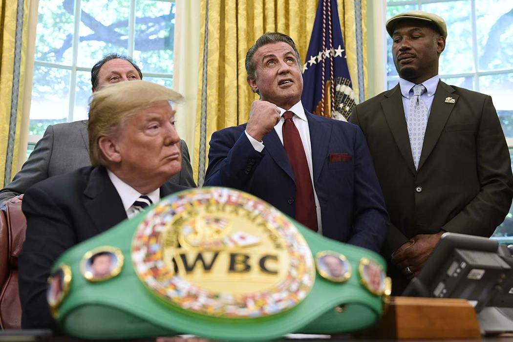 President Donald Trump, left, and heavyweight champion boxer, Lennox Lewis, right, watch as Sylvester Stallone gestures in the Oval Office of the White House in Washington, Thursday, May 24, 2018, ...