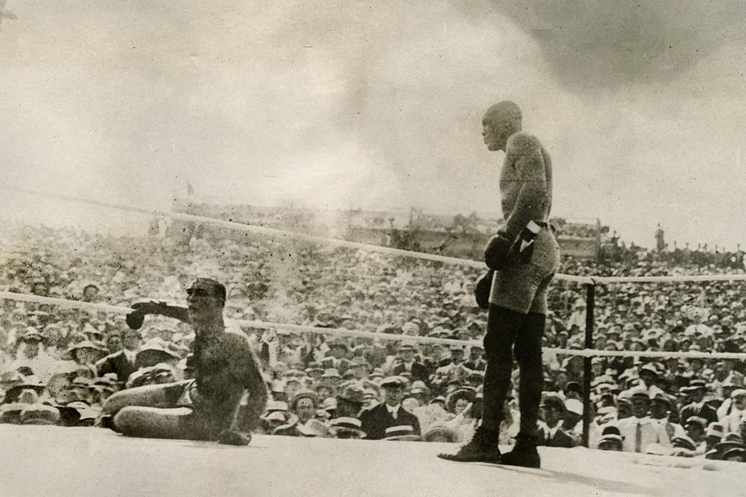 In this July 4, 1910 file photo, provided by the Nevada Historical Society, Jack Johnson, right, knocks out Jim Jeffries during a boxing match in Reno, Nev. A century ago Johnson reached the pin ...