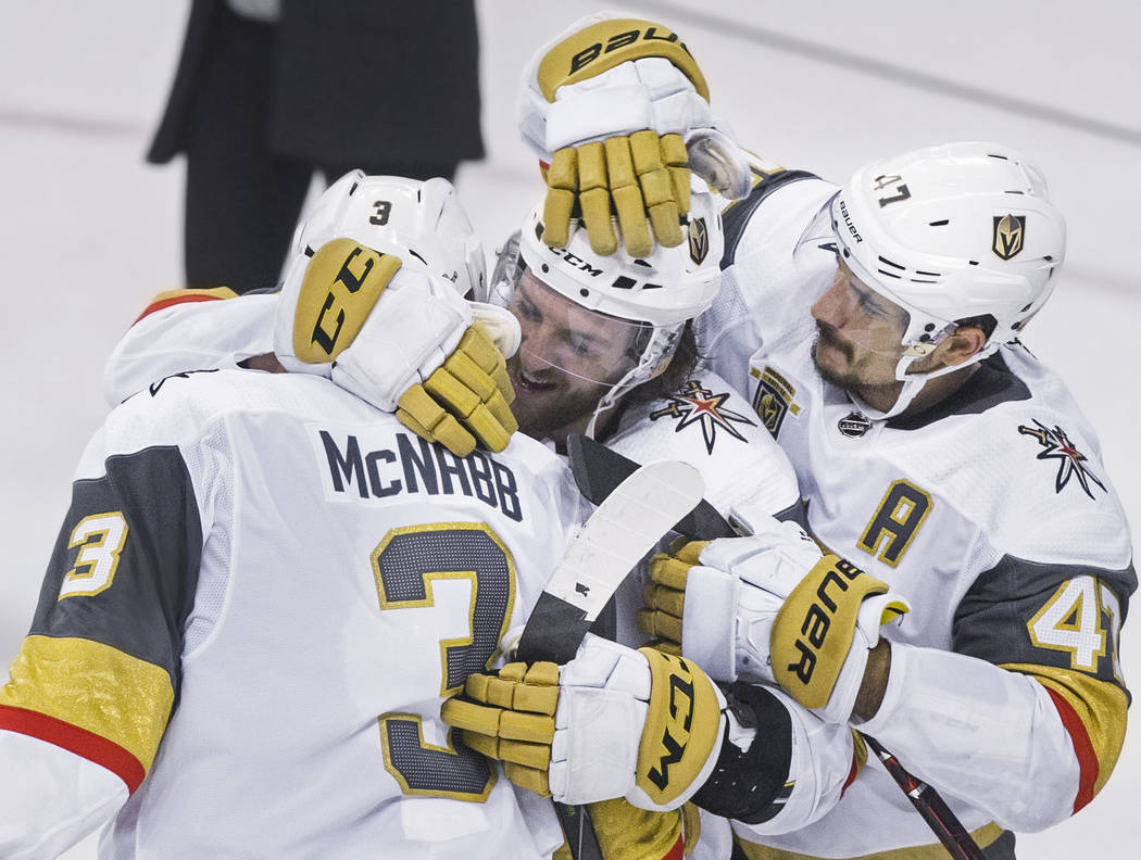 Golden Knights defenseman Brayden McNabb (3) gets a hug from teammates Colin Miller (6) and Luca Sbisa (47) after beating the Winnipeg Jets 2-1 to advance to the Stanley Cup Finals on Sunday, May ...