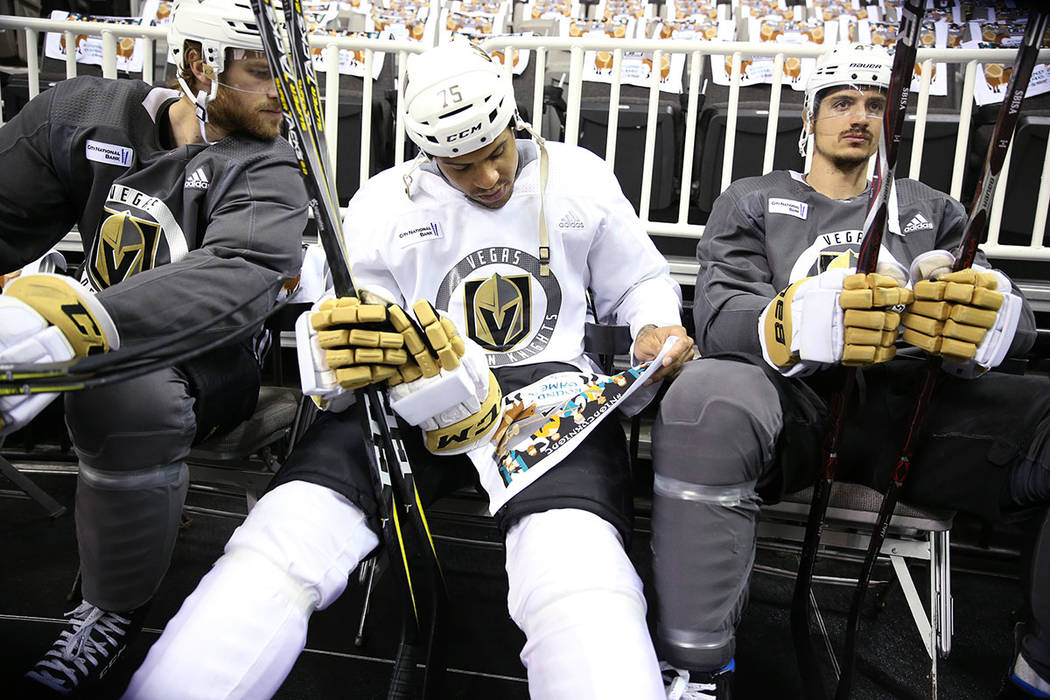 Vegas Golden Knights right wing Ryan Reaves (75), center, looks at a rally towel before taking the ice for practice with defenseman Jon Merrill (15), left, and defenseman Luca Sbisa (47), at the S ...