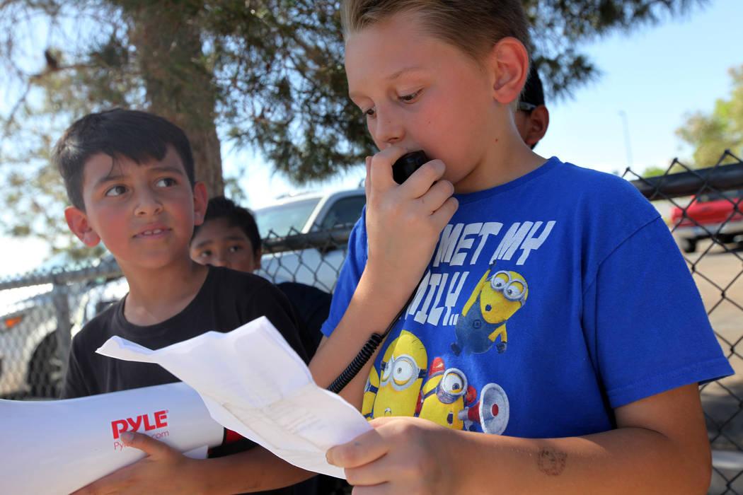 Ryan Brady, 10, speaks about grievances over CCSD budget cuts and other issues as Adrian Hinojosa, 9, listens during a town hall outside of Stanford Elementary School in Las Vegas, Wednesday, May ...