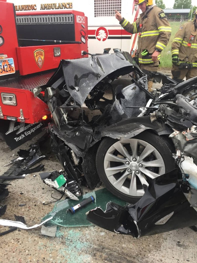 A traffic collision involving a Tesla Model S sedan with a Fire Department mechanic truck stopped at a red light is seen in South Jordan, Utah., on May 11. (South Jordan Police Department via AP)