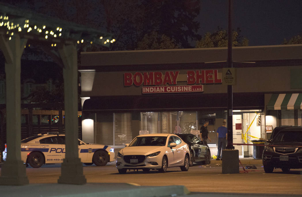 Police stand outside the Bombay Bhel restaurant in Mississauga, Canada Friday, May 25, 2018. Canadian police say an explosion set off deliberately in a restaurant has wounded a number of people. ( ...