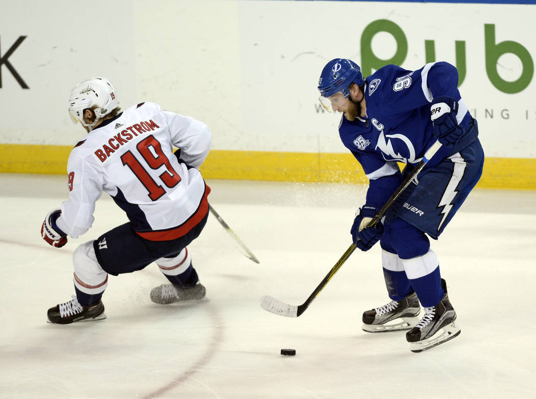 Tampa Bay Lightning center Steven Stamkos, right, moves the puck around Washington Capitals center Nicklas Backstrom (19) during the first period of Game 7 of the NHL Eastern Conference finals hoc ...