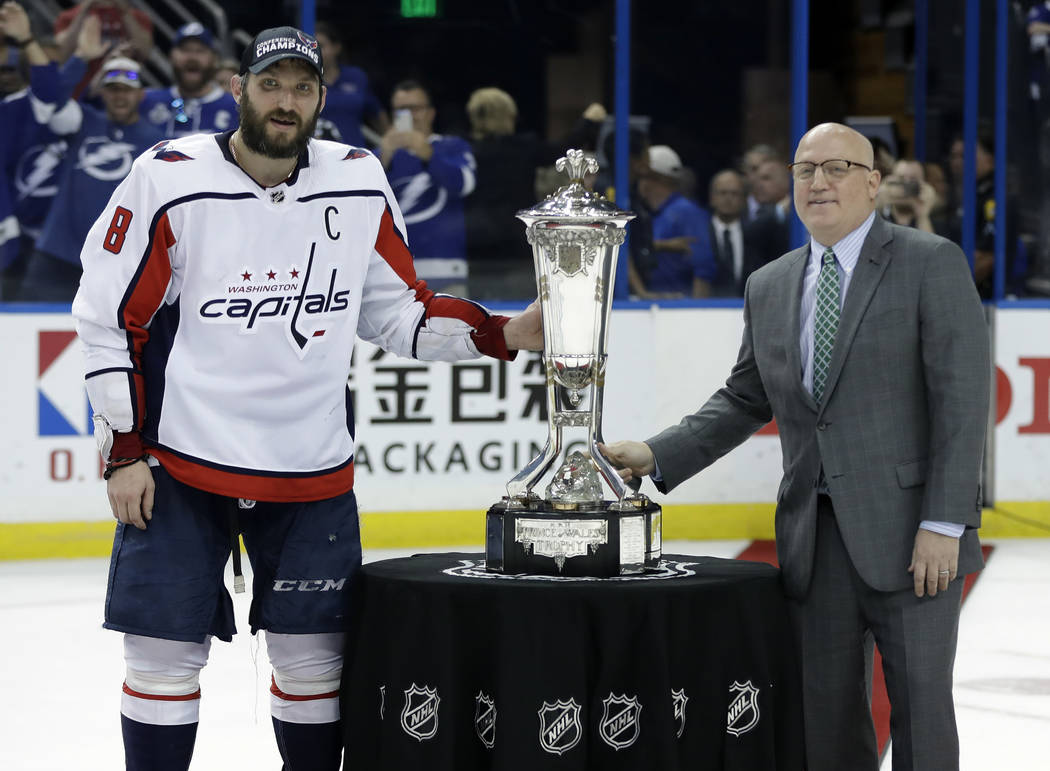 Washington Capitals left wing Alex Ovechkin, left, poses with NHL Deputy Commissioner Bill Daly and the Prince of Wales trophy after the Capitals defeated the Tampa Bay Lightning 4-0 during Game 7 ...