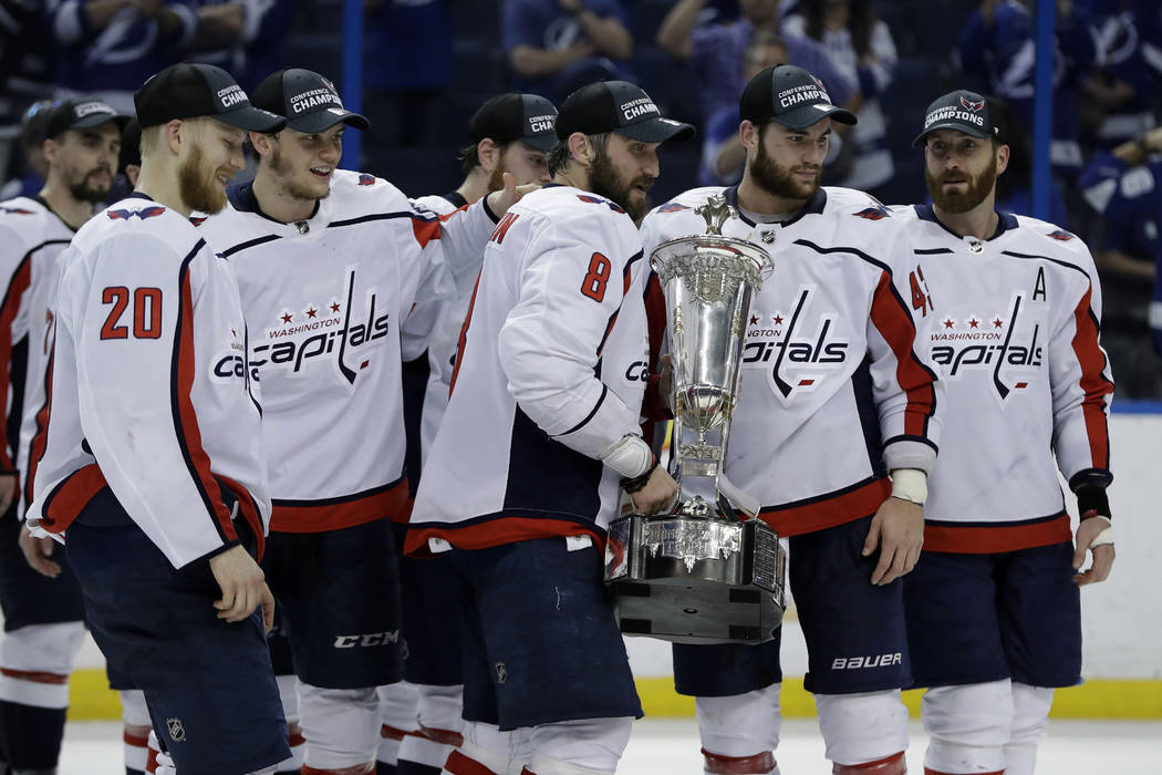 Washington Capitals left wing Alex Ovechkin (8) holds the Prince of Wales trophy with teammates after the Capitals defeated the Tampa Bay Lightning 4-0 during Game 7 of the NHL Eastern Conference ...