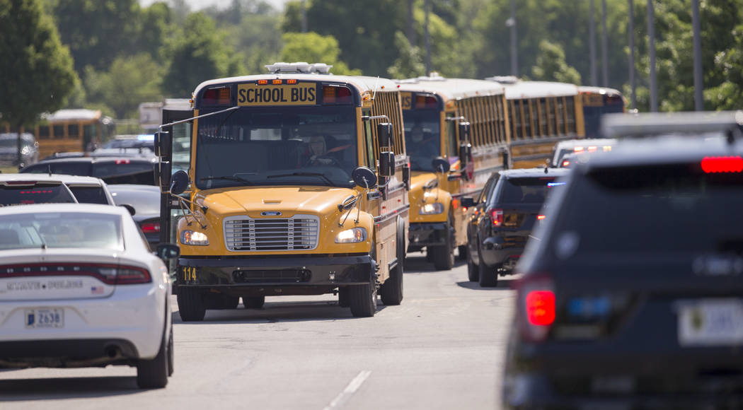 Empty school buses leave after a shooting at Noblesville West Middle School in Noblesville Ind. on Friday