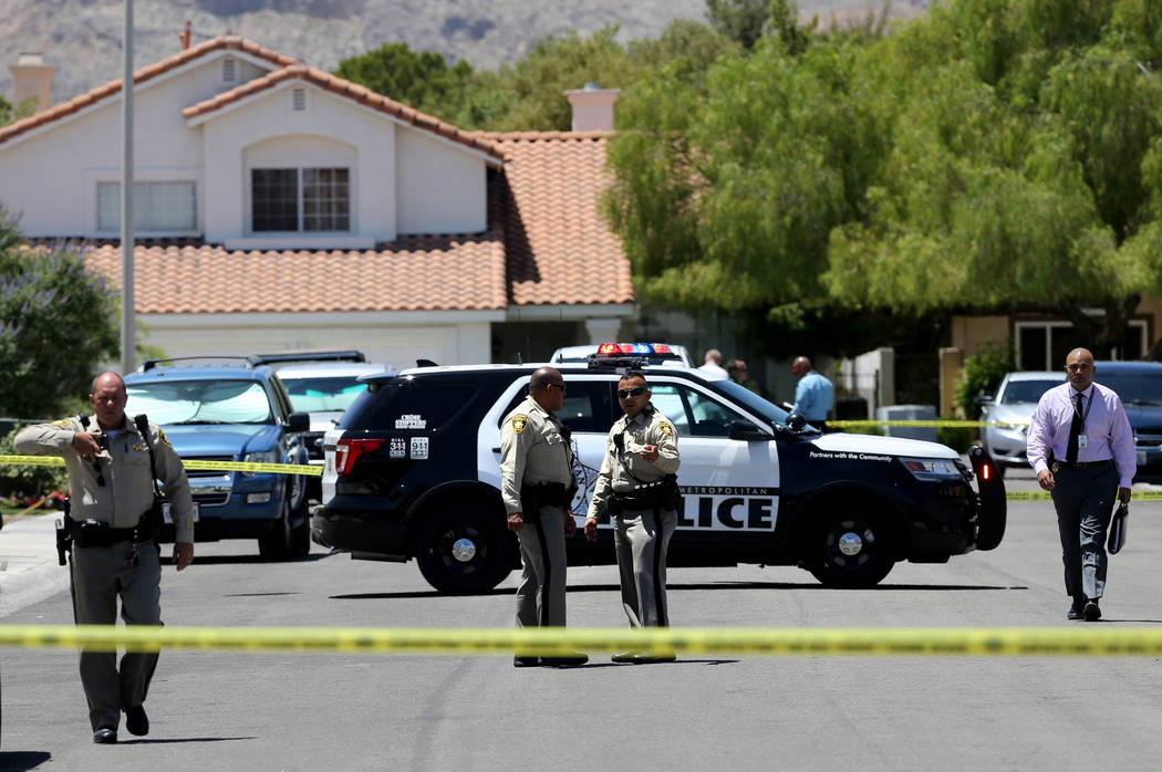 Las Vegas police investigate at the scene of a deadly shooting in a home near Sahara Avenue and Hualapai Way on Thursday, May 24, 2018. Police said a 15-year-old boy shot and killed his father, th ...