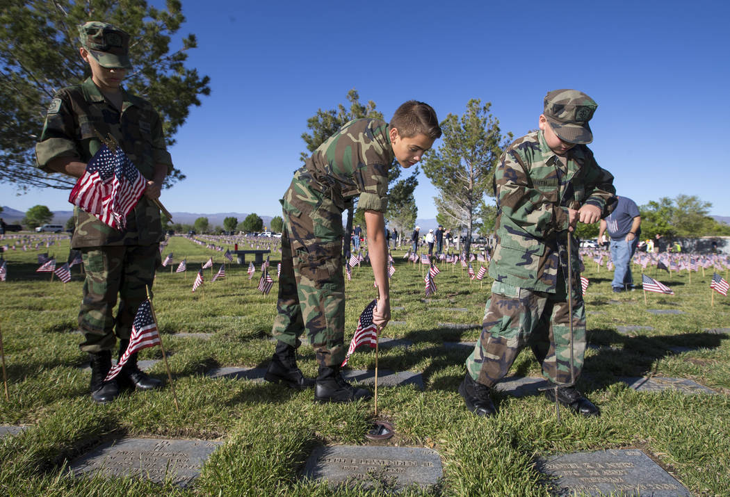 Members of the United States Naval Sea Cadet Corps, from left, Aiden Stewart, Julian Mejia, and Vaden Smith work to place flags at gravesites at the Southern Nevada Veterans Memorial Cemetery in B ...