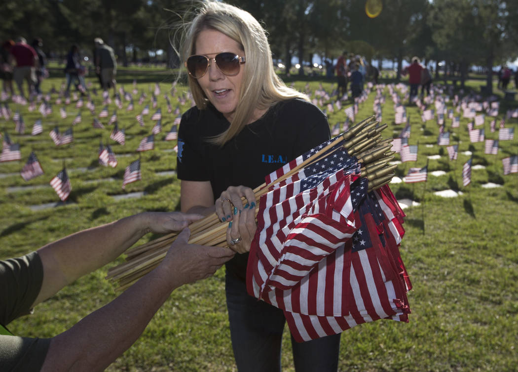 Las Vegas resident Michelle Goldyn works to place flags at gravesites at the Southern Nevada Veterans Memorial Cemetery in Boulder City on Saturday, May 26, 2018. Richard Brian Las Vegas Review-Jo ...
