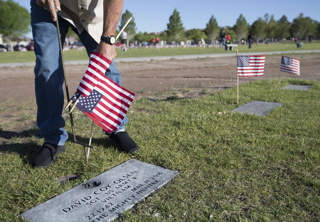 Las Vegas resident Andy LeDuc works to place flags at a gravesites at the Southern Nevada Veterans Memorial Cemetery in Boulder City on Saturday, May 26, 2018. Richard Brian Las Vegas Review-Journ ...