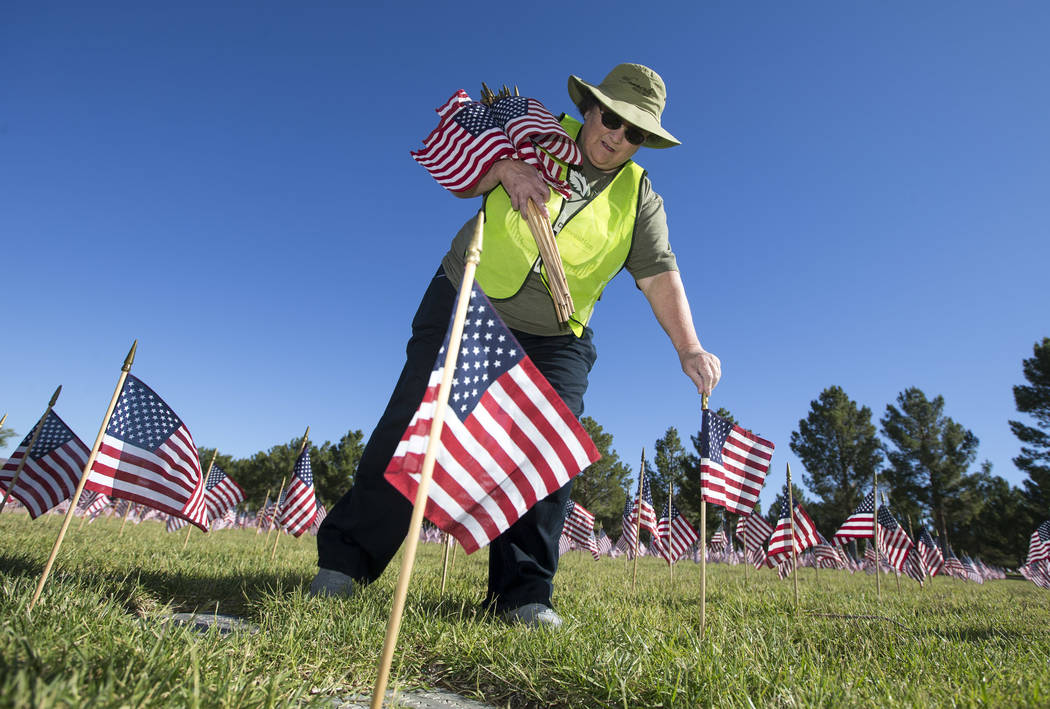 Volunteer Iris Brzezinski, with Disabled American Veterans Auxiliary, works to place flags at a gravesites at the Southern Nevada Veterans Memorial Cemetery in Boulder City on Saturday, May 26, 20 ...