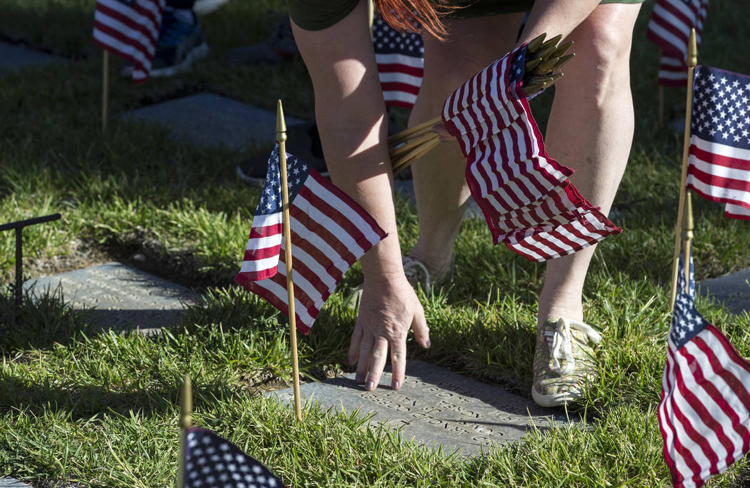 Las Vegas resident Ingrid Evenson rubs her hand on the headstone of U.S. Navy veteran Lloyd Arnold Coffey, Jr. as she and hundreds of volunteers worked to place flags at gravesites at the Southern ...
