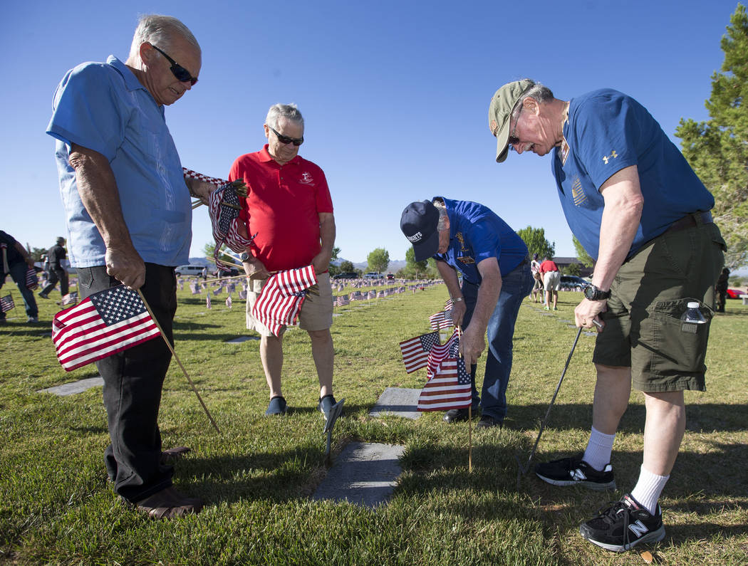 Members of St. Francis of Assisi Catholic Church, from left, Mike Towle, Tony Williams, Patrick Hanley and John Seaquist work to place flags at gravesites at the Southern Nevada Veterans Memorial ...