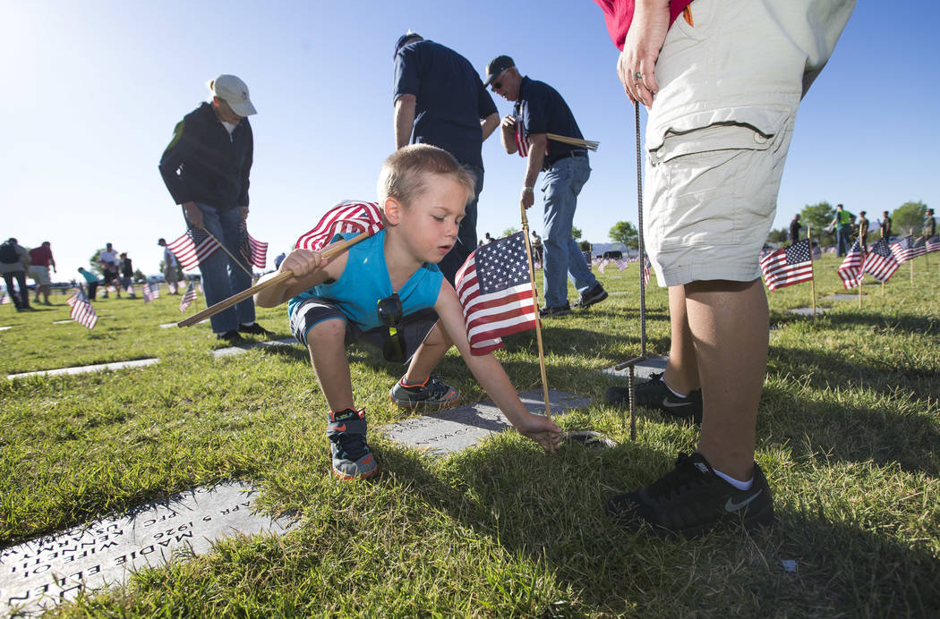 Four-year-old Alex Chavez places a flag at a gravesite at the Southern Nevada Veterans Memorial Cemetery in Boulder City on Saturday, May 26, 2018. Richard Brian Las Vegas Review-Journal @vegaspho ...