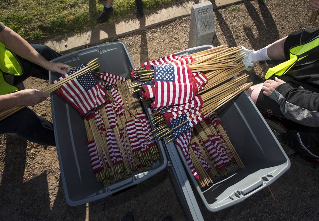 Volunteers work to place flags at gravesites at the Southern Nevada Veterans Memorial Cemetery in Boulder City on Saturday, May 26, 2018. Richard Brian Las Vegas Review-Journal @vegasphotograph