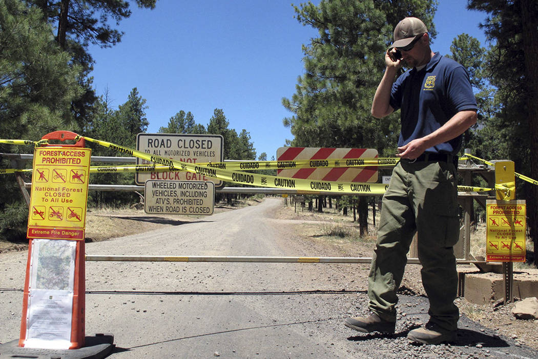 Matt Engbring, a fire prevention officer with the U.S. Forest Service, checks on signs Thursday that alert the public to closures in parts of the national forest surrounding Flagstaff, Ariz. (AP P ...