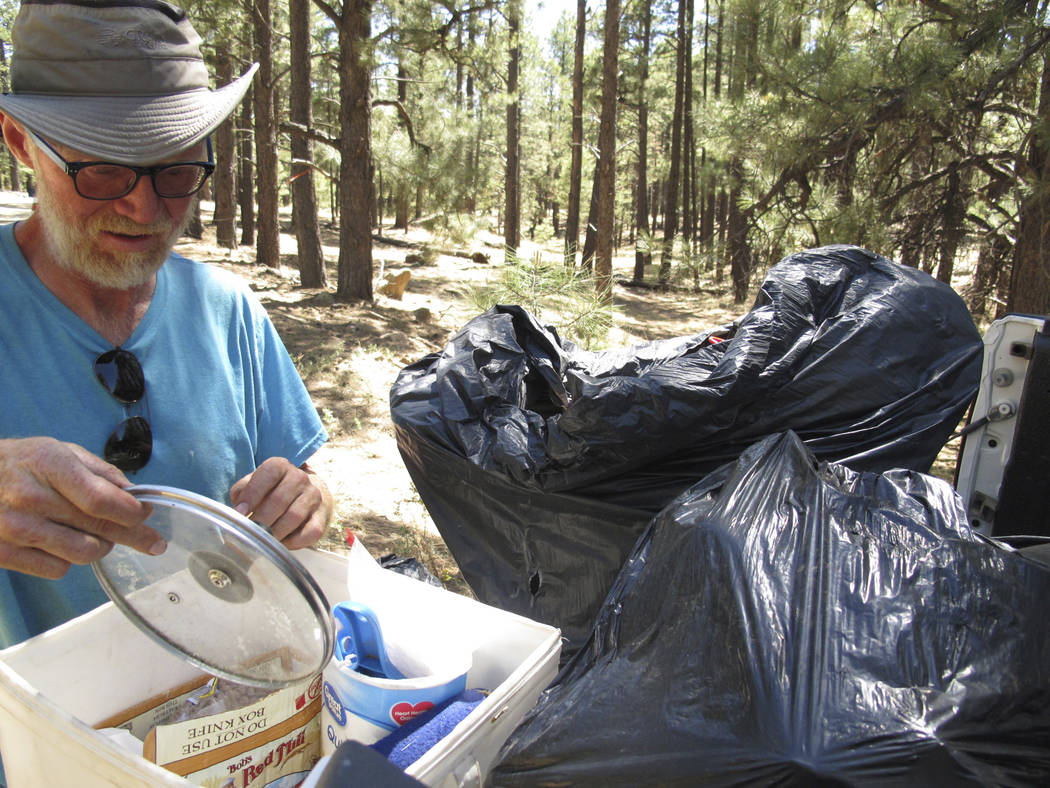 John Dobson combs through his belongings from a site in the national forest outside Flagstaff, Ariz., on Thursday. (AP Photo/Felicia Fonseca)