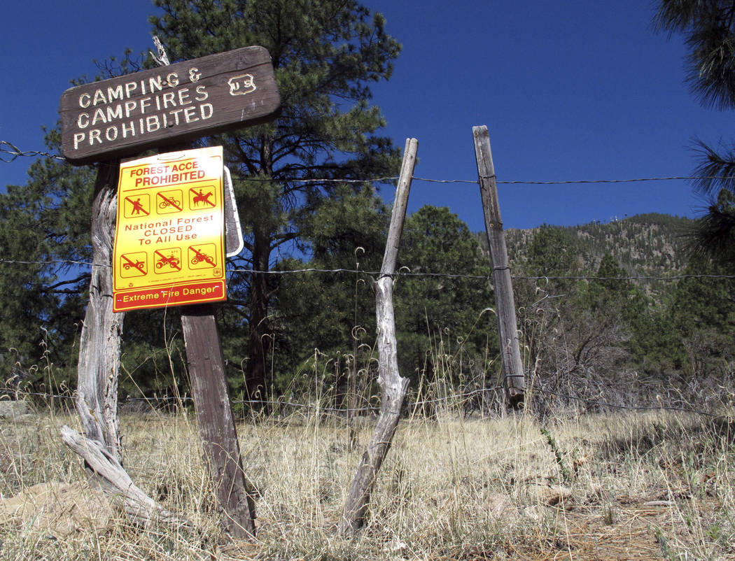 A sign posted at a trail leading into the national forest in Flagstaff, Ariz., tells the public no one is allowed in. M(AP Photo/Felicia Fonseca)