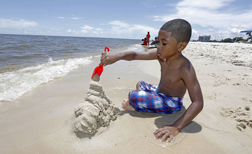 Tyler Ray Wells, 4, builds a sand castle by the water on Biloxi Beach in Biloxi, Miss., Saturday, May 26, 2018, as Subtropical Storm Alberto slowly makes its way through the Gulf of Mexico. (AP Ph ...