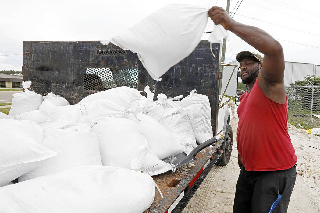 Travis Lee loads filled sand bags onto a truck bed as he and a co-worker prepare to protect the storage company they work at, Saturday, May 26, 2018 in Gulfport, Miss. (AP Photo/Rogelio V. Solis)