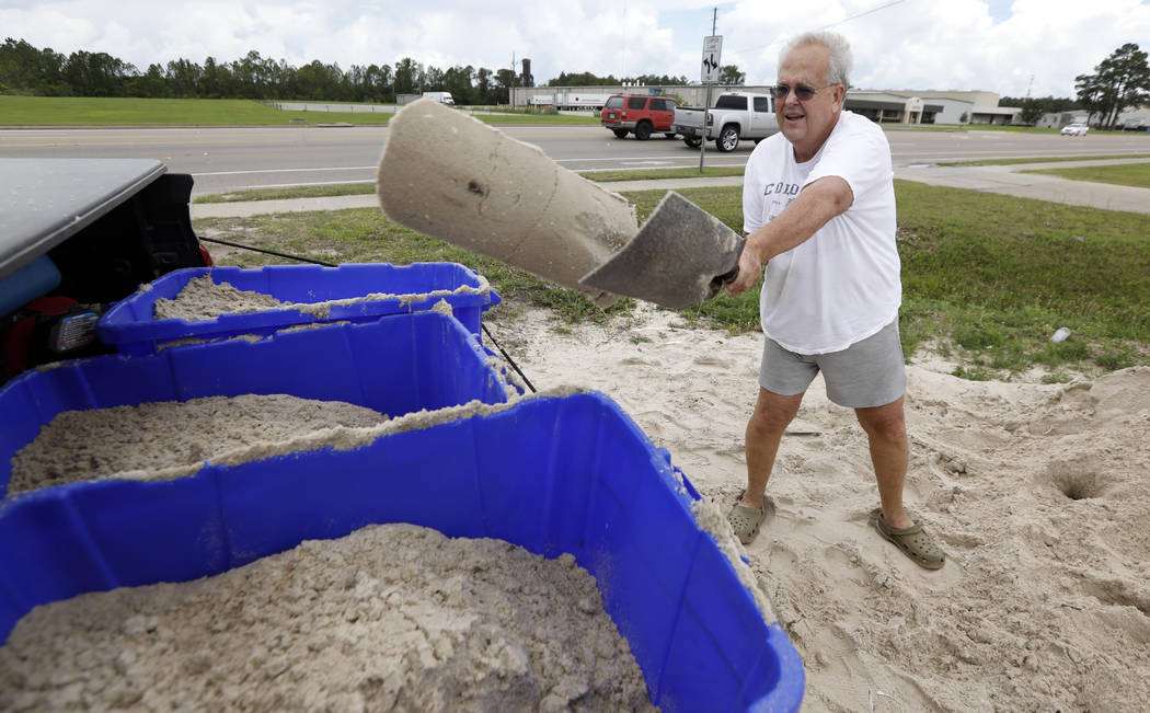 George Estes tosses sand into storage tubs at a Harrison County Road Department sand bagging location, that he will take back to his law office in downtown Gulfport, Miss., and will enlist help to ...