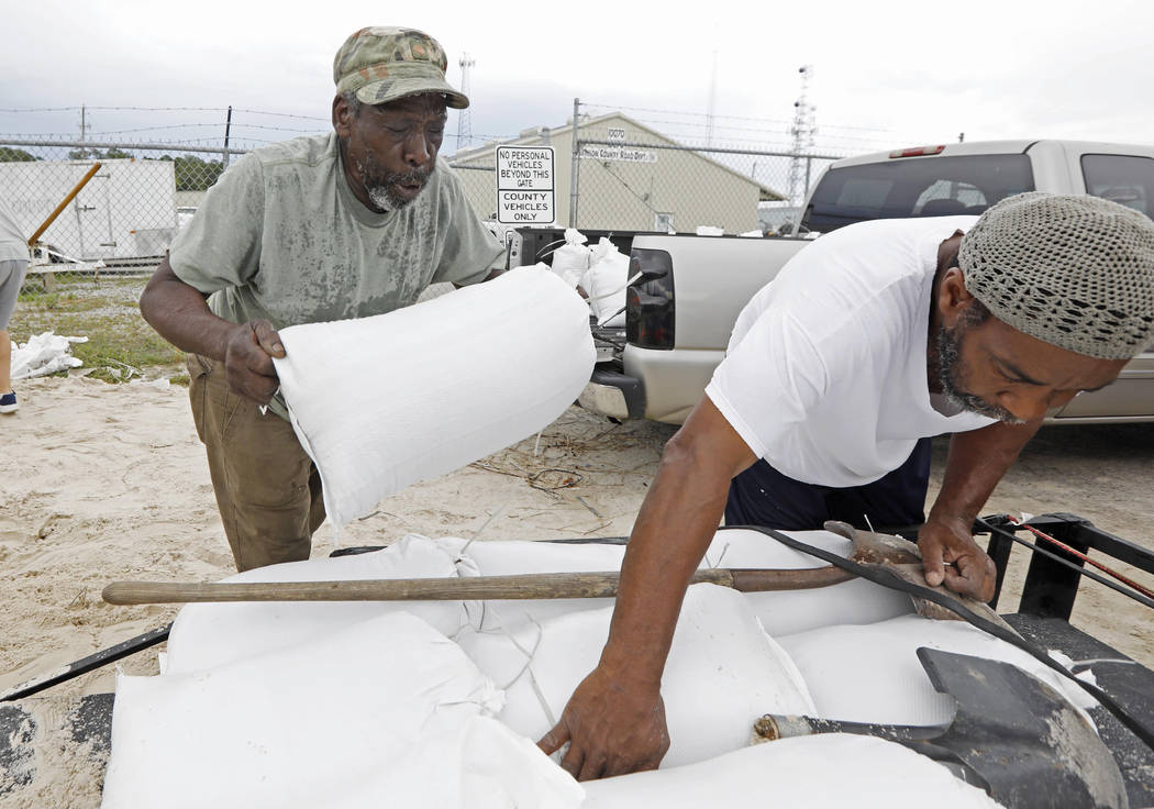 Tommy Whitlock, left, places a filled sand bag onto his trailer at a Harrison County Road Department sand bag location, as his friend Joseph Buckner adjusts the load while preparing for Subtropica ...