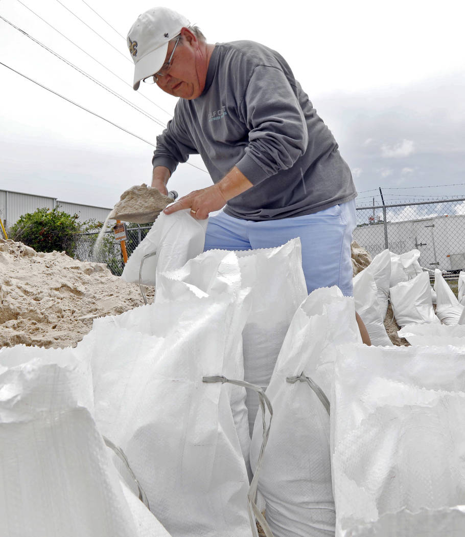 Eddy Warner loads sand bags as he waits for family members to assist and tie off and load the bags into his vehicle while preparing for Subtropical Storm Alberto to make its way through the Gulf