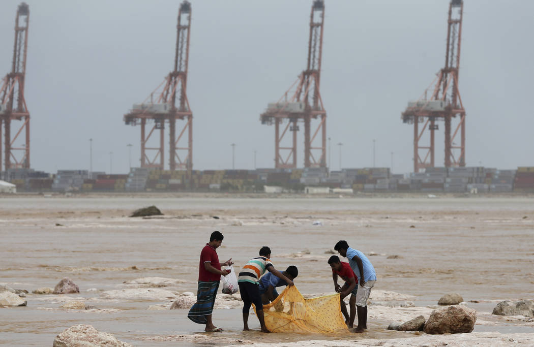 Asian workers enjoy fishing in the flood water after Cyclone Merkunu in Salalah, Oman, Saturday, May 26, 2018. Cyclone Merkunu blew into the Arabian Peninsula on Saturday, drenching arid Oman and ...