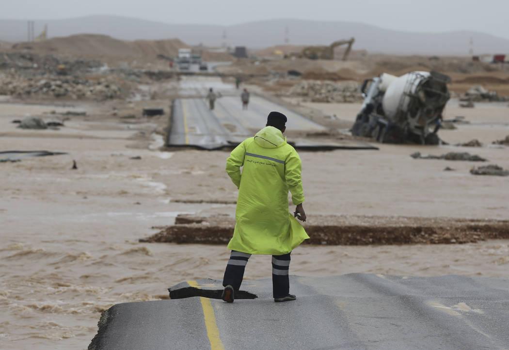 An Omani civil defence staff visits a road which has been cut by the flood water after Cyclone Merkunu in Salalah, Oman, Saturday, May 26, 2018. Cyclone Merkunu blew into the Arabian Peninsula on ...