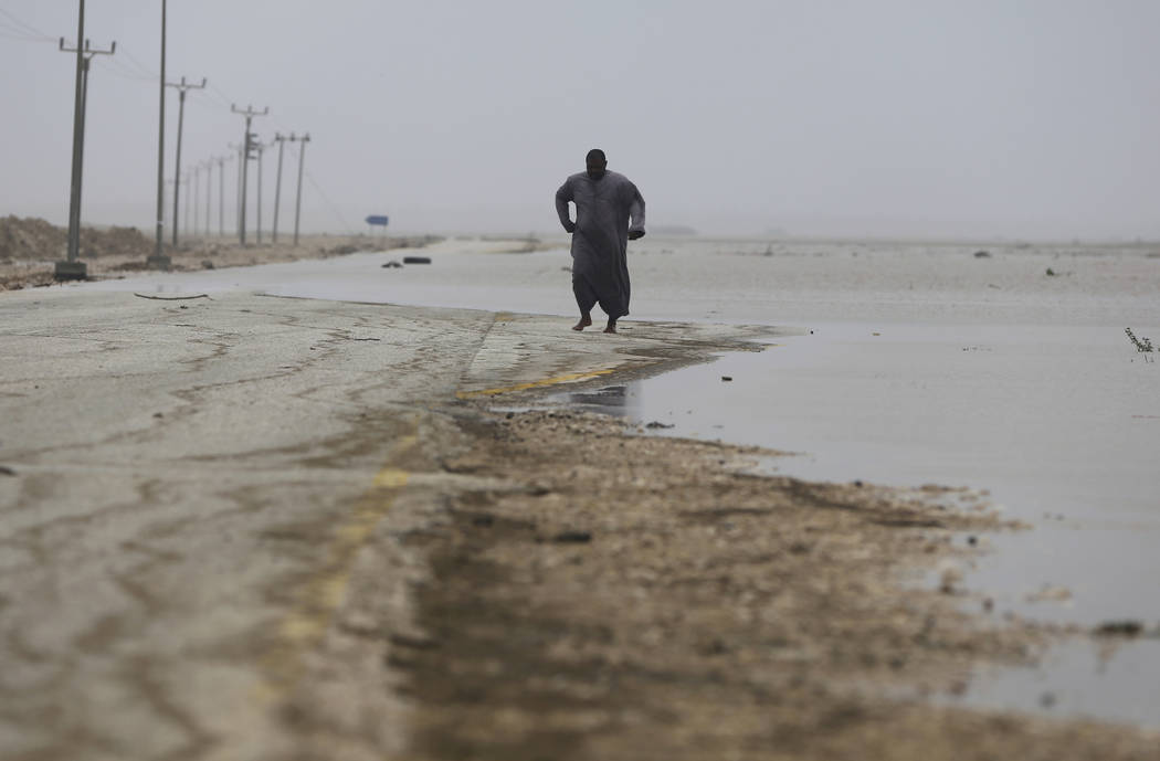 An Omani man walks on the road covered by the flood water after Cyclone Merkunu in Salalah, Oman, Saturday, May 26, 2018. Cyclone Merkunu blew into the Arabian Peninsula on Saturday, drenching ari ...