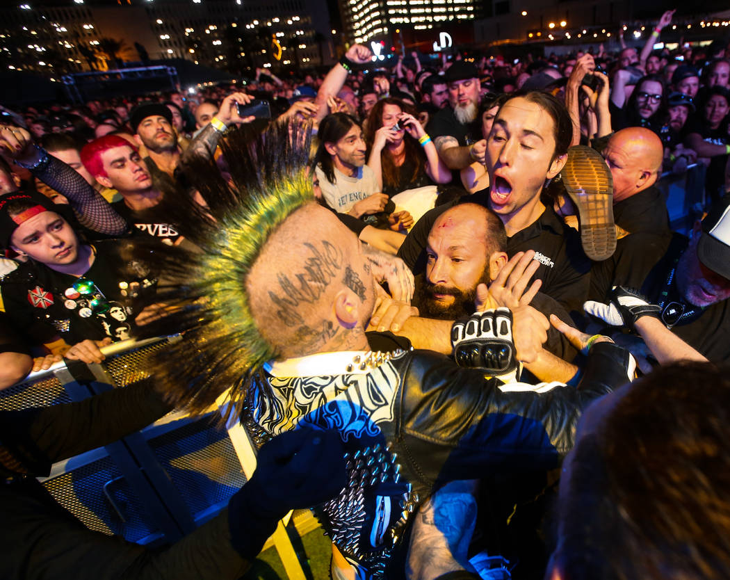 A security guard tries to break up a pair of attendees that jumped over the barricade during the first day of the Punk Rock Bowling music festival in downtown Las Vegas on Saturday, May 26, 2018. ...