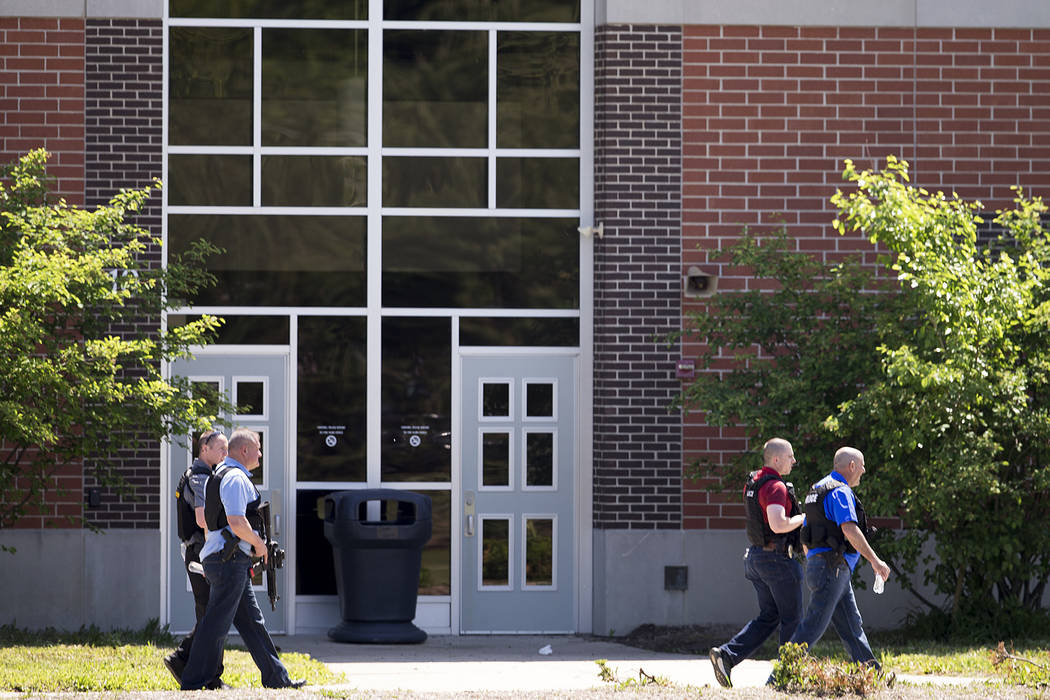 Law enforcement officers walk outside Noblesville West Middle School in Noblesville, Ind., after a shooting on Friday, May 25, 2018. A male student opened fire at the suburban Indianapolis school ...