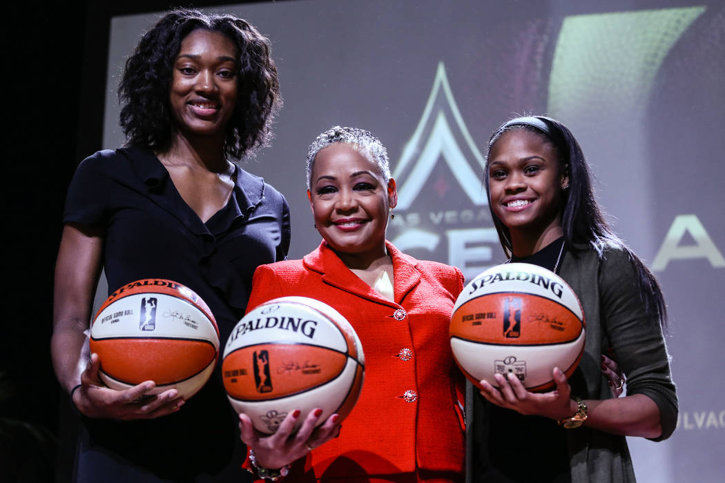 Las Vegas Aces' Kayla Janine Alexander, left, WNBA President Lisa Borders, center, Las Vegas Aces' Moriah Jefferson, right, gather during the reveal of the Las Vegas Aces WNBA basketball team at t ...