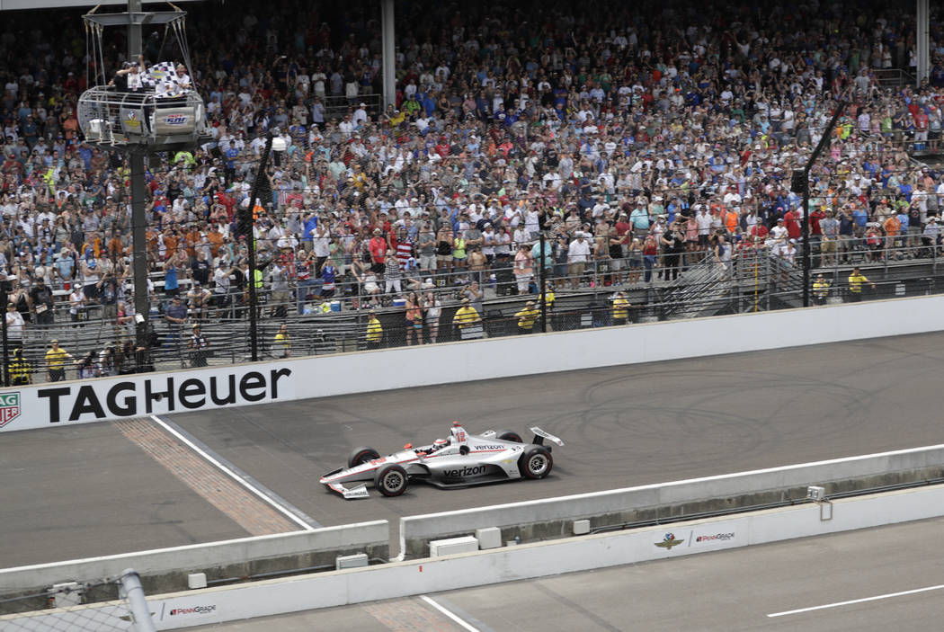Will Power, of Australia, takes the checkered flag to win the Indianapolis 500 auto race at Indianapolis Motor Speedway in Indianapolis, Sunday, May 27, 2018. (AP Photo/Dave Parker)