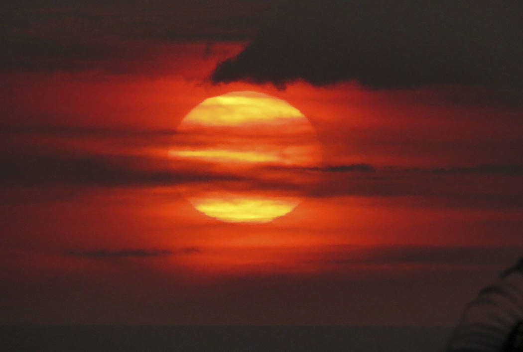 "The sun sets through ""vog,"" or volcanic smog, in Kailua-Kona, Hawaii. (Chris Stewart via AP)"
