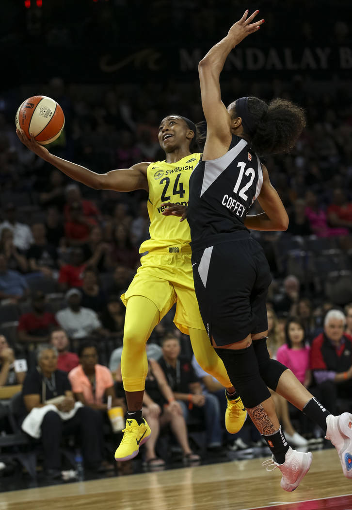 Seattle Storm guard Jewell Loyd (24) goes up for a shot against Las Vegas Aces forward Nia Coffey (12) in the first half of a WNBA basketball game at the Mandalay Bay Events Center in Las Vegas on ...