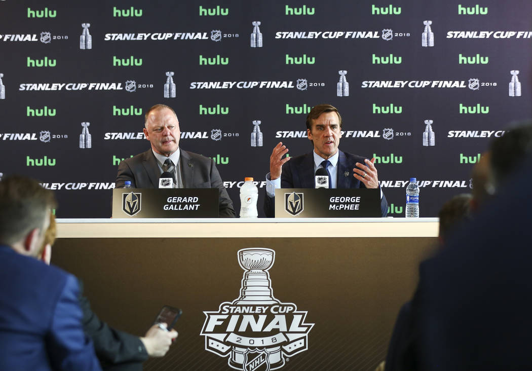 Golden Knights head coach Gerard Gallant, left, looks on as George McPhee, general manager of the team, speaks during NHL hockey media day for the Stanley Cup Final at the T-Mobile Arena in Las Ve ...