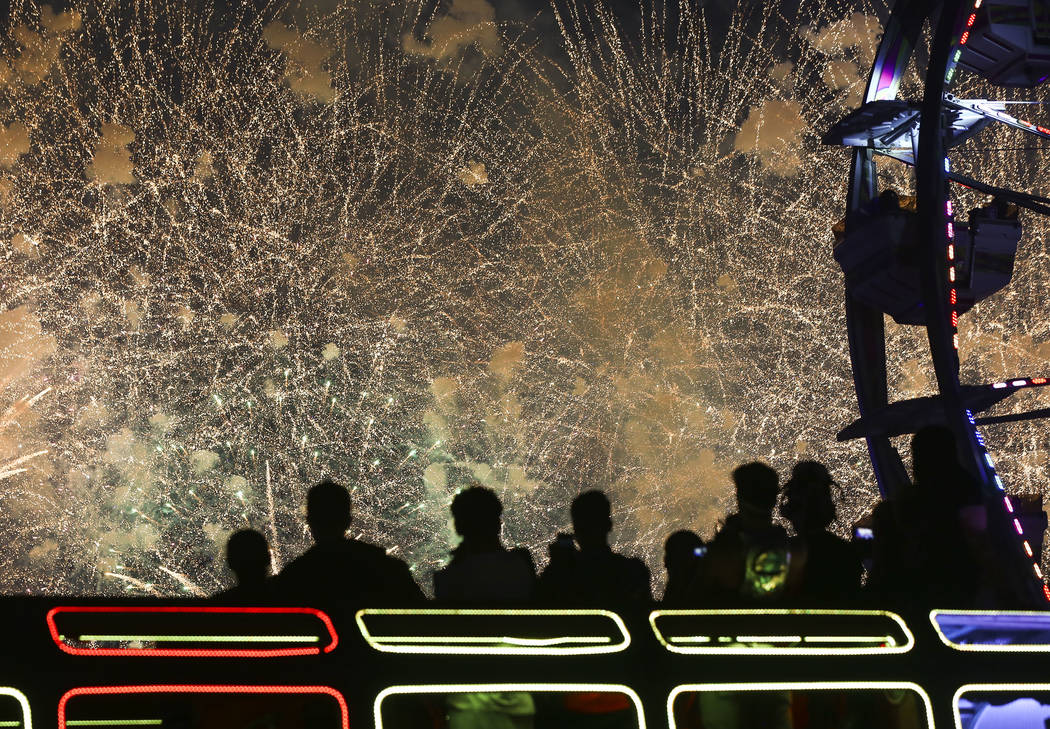 Attendees watch fireworks from atop an art car during the third day of the Electric Daisy Carnival at the Las Vegas Motor Speedway in Las Vegas during the early hours of Monday, May 21, 2018. Chas ...