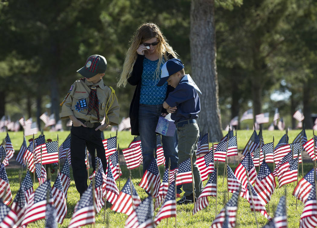Boulder City resident Kelly P., center, who declined to give her last name, and her children, Gage, 9, and Colton, 7, visit the headstone of Kelly's grandfather, Korean and Vietnam veteran Frank T ...