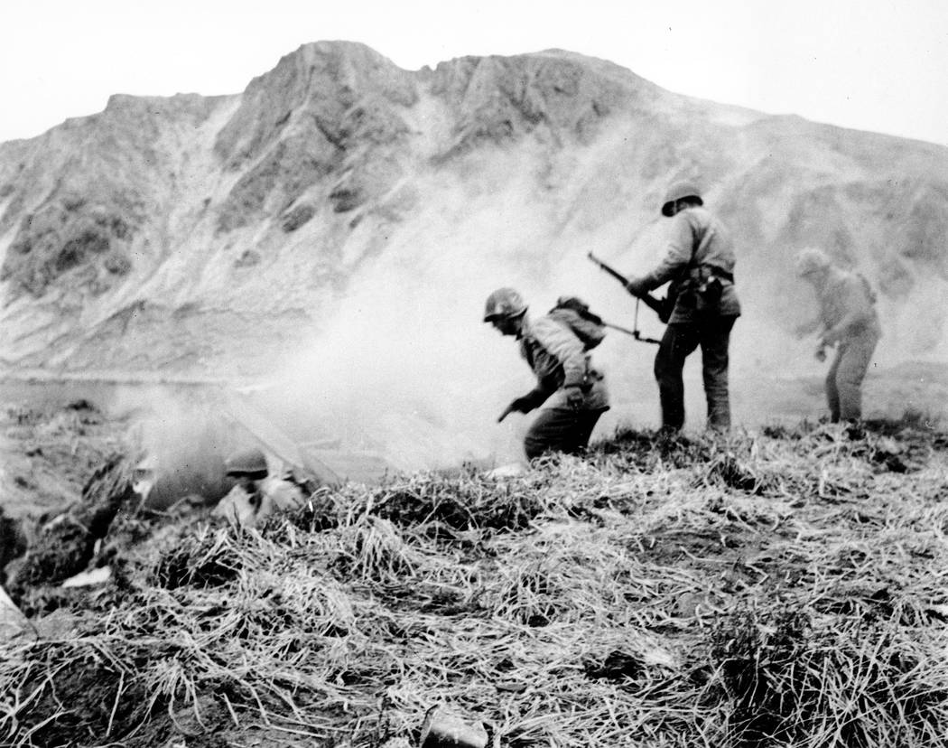 FILE - In this June 1943 file photo, a U.S. squad armed with guns and hand grenades close in on Japanese holdouts entrenched in dugouts during World War II on Attu Island, part of the Aleutian Isl ...