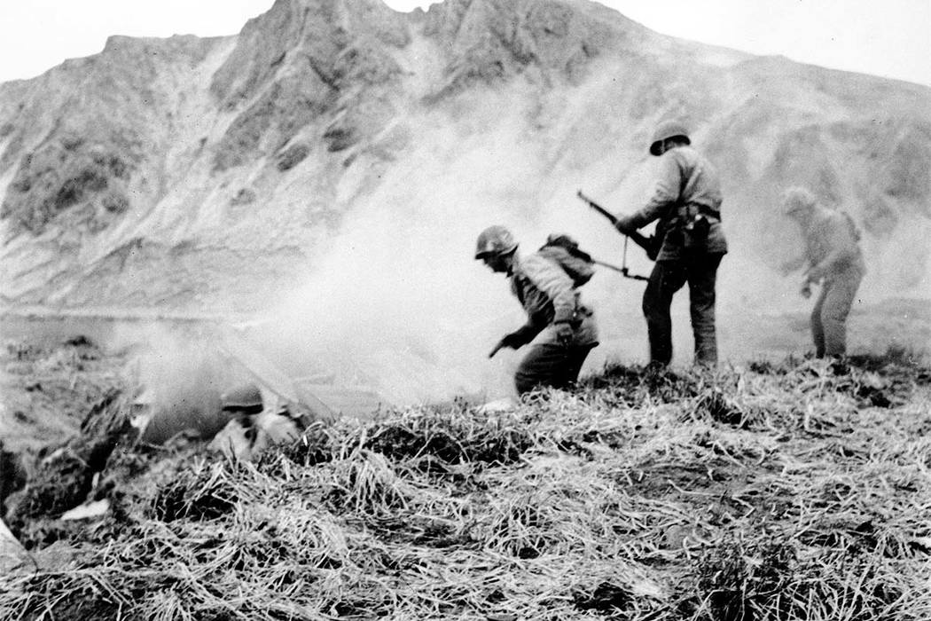 In this June 1943 file photo, a U.S. squad armed with guns and hand grenades close in on Japanese holdouts entrenched in dugouts during World War II on Attu Island, part of the Aleutian Islands of ...