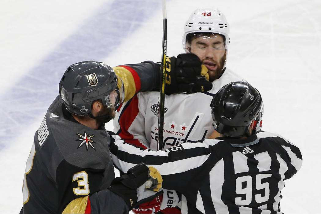 Vegas Golden Knights defenseman Brayden McNabb, left, hits Washington Capitals right wing Tom Wilson as linesman Jonny Murray tries to break it up during the third period in Game 1 of the NHL hock ...