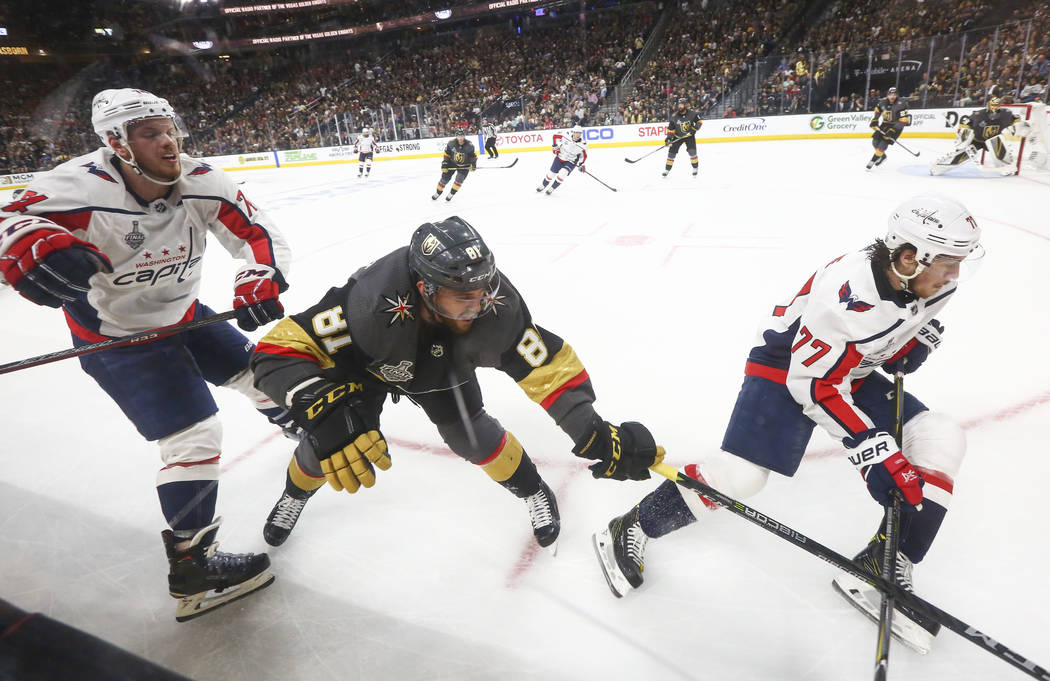 Golden Knights center Jonathan Marchessault (81) battles for the puck between Washington Capitals defenseman John Carlson (74) and right wing T.J. Oshie (77) during the second period of Game 1 of ...