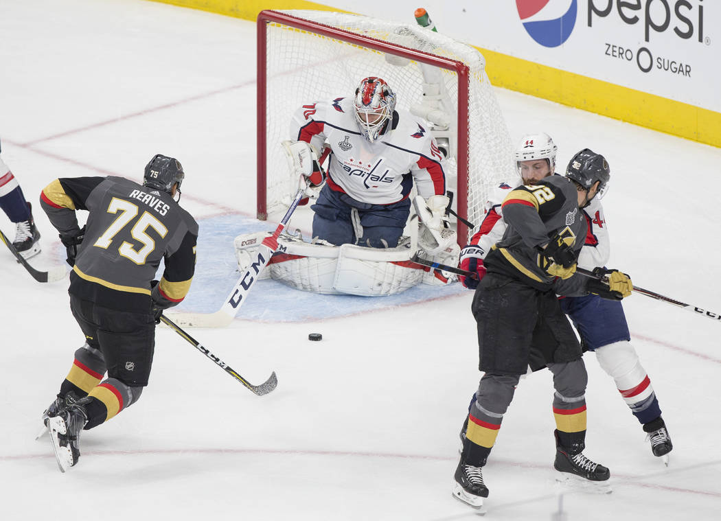 Capitals goaltender Braden Holtby (70) makes a first-period save against Golden Knights right wing Ryan Reaves (75) during Game 1 of the NHL Stanley Cup Finals on Monday, May 28, 2018, at T-Mobile ...