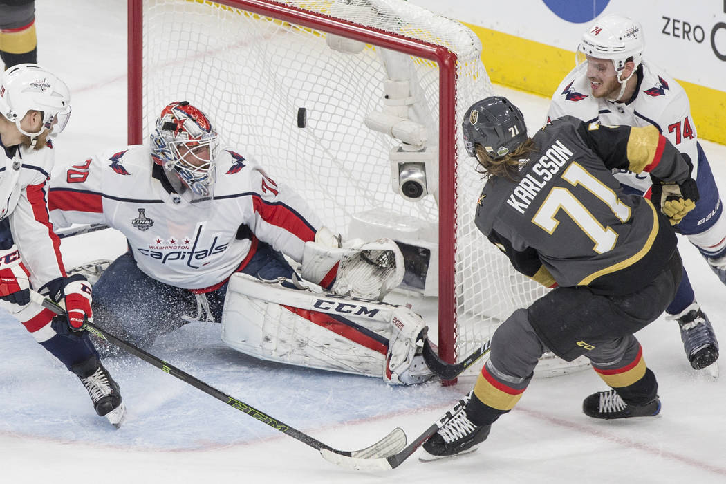 Golden Knights center William Karlsson (71) scores a first-period goal against Capitals goaltender Braden Holtby (70) during Game 1 of the NHL Stanley Cup Finals on Monday, May 28, 2018, at T-Mobi ...